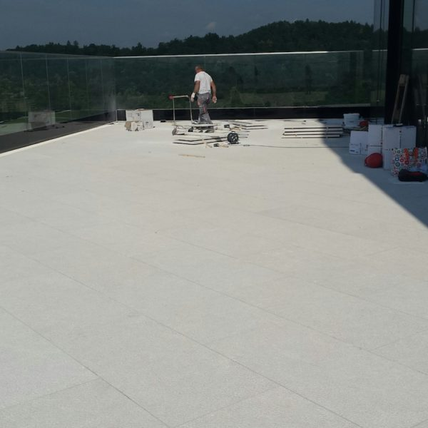 Hotel Rooftop Decking Application with Buzon Pedestals Supporting Porcelain Pavers - HDG Building Materials