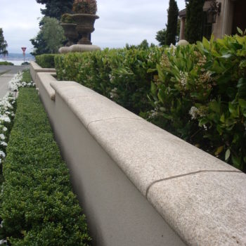 image of Curved and Finished Coping Stone Atop Natural Stone Wall in Landscape Design - HDG Building Materials