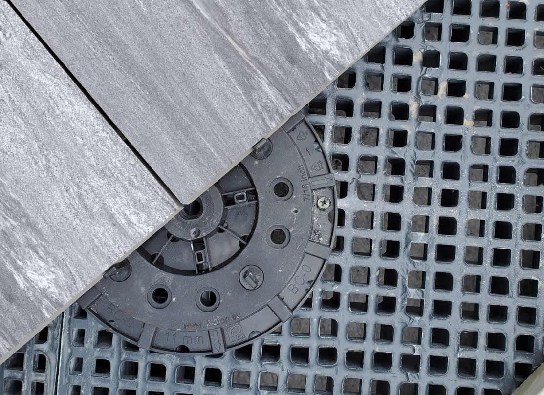 HDG Silpova Grey 3CM Porcelain Paver with Light Grey Veign-Cut Sandstone Finish - Porcelain Paver over Buzon Pedestal on top of HDG FRP Grating - HDG Building Materials