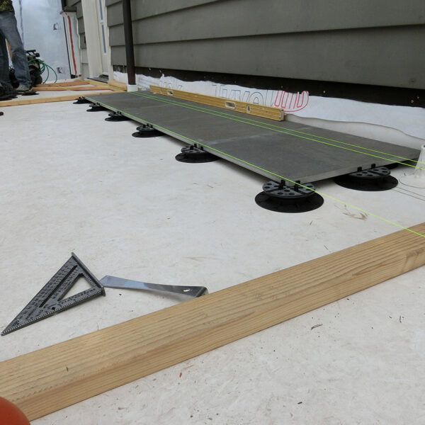 Installing First Row of Porcelain Pavers Over Buzon Pedestals on Deck - HDG Building Materials